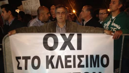 """A man holds a protest sign that says """" no to the shutting down of banks"""""""